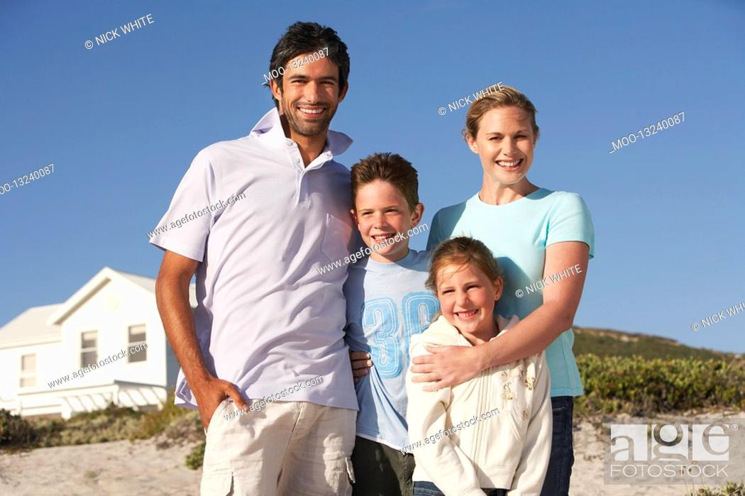 Stock Photo: Family standing on beach smiling beach house behind.