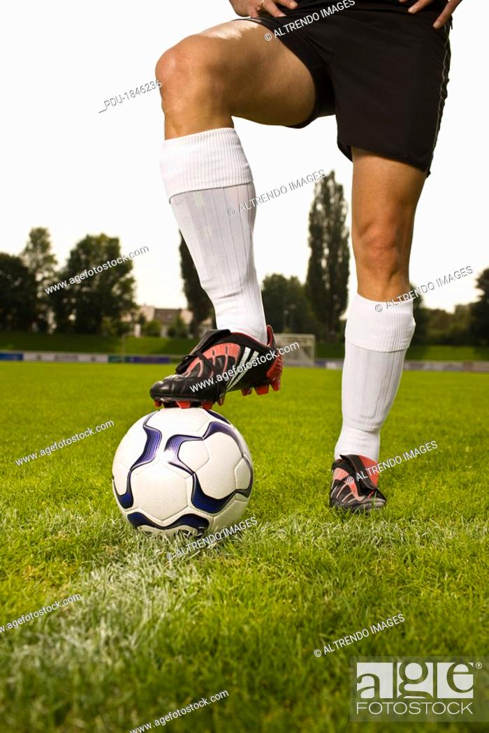 Stock Photo: Man in soccer uniform standing with soccer ball on grass.