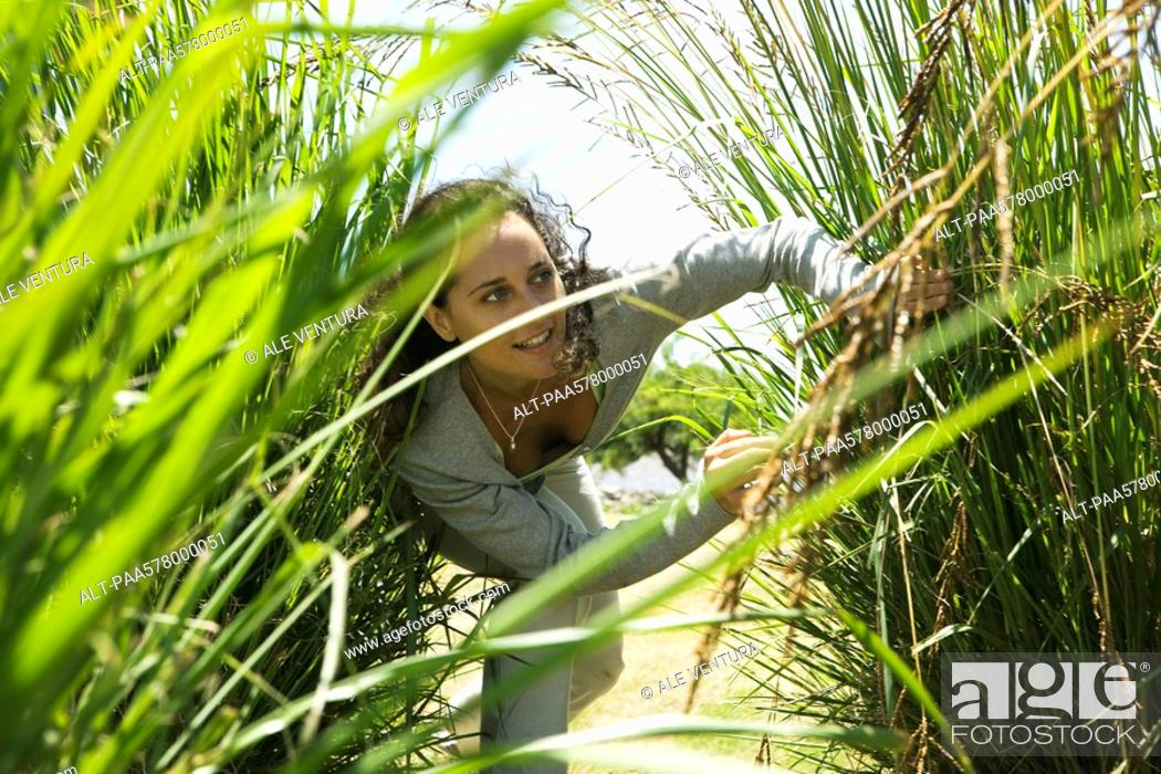Stock Photo: Woman hiding in tall grass.