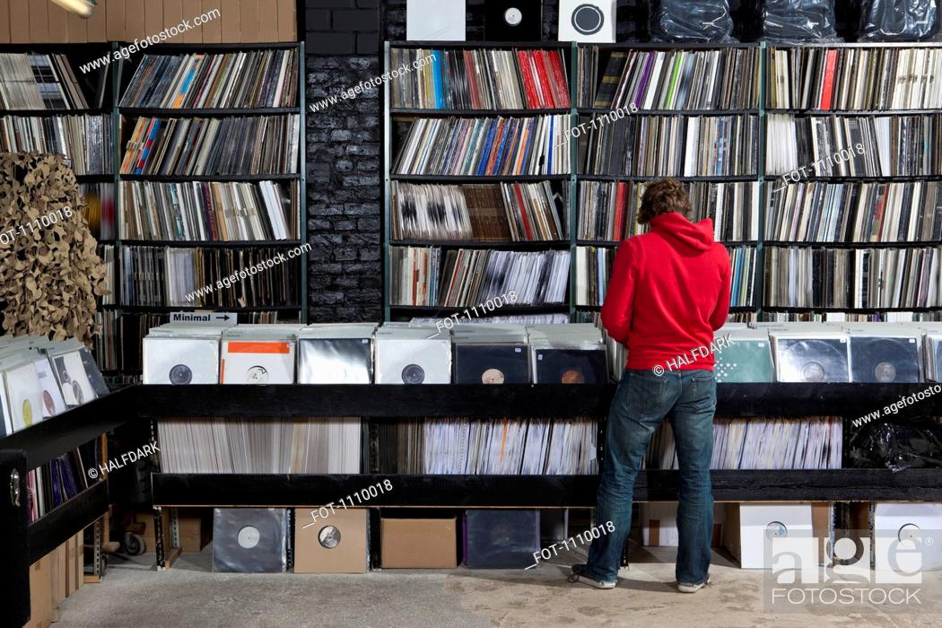 Stock Photo: Rear view of young man in a record store.