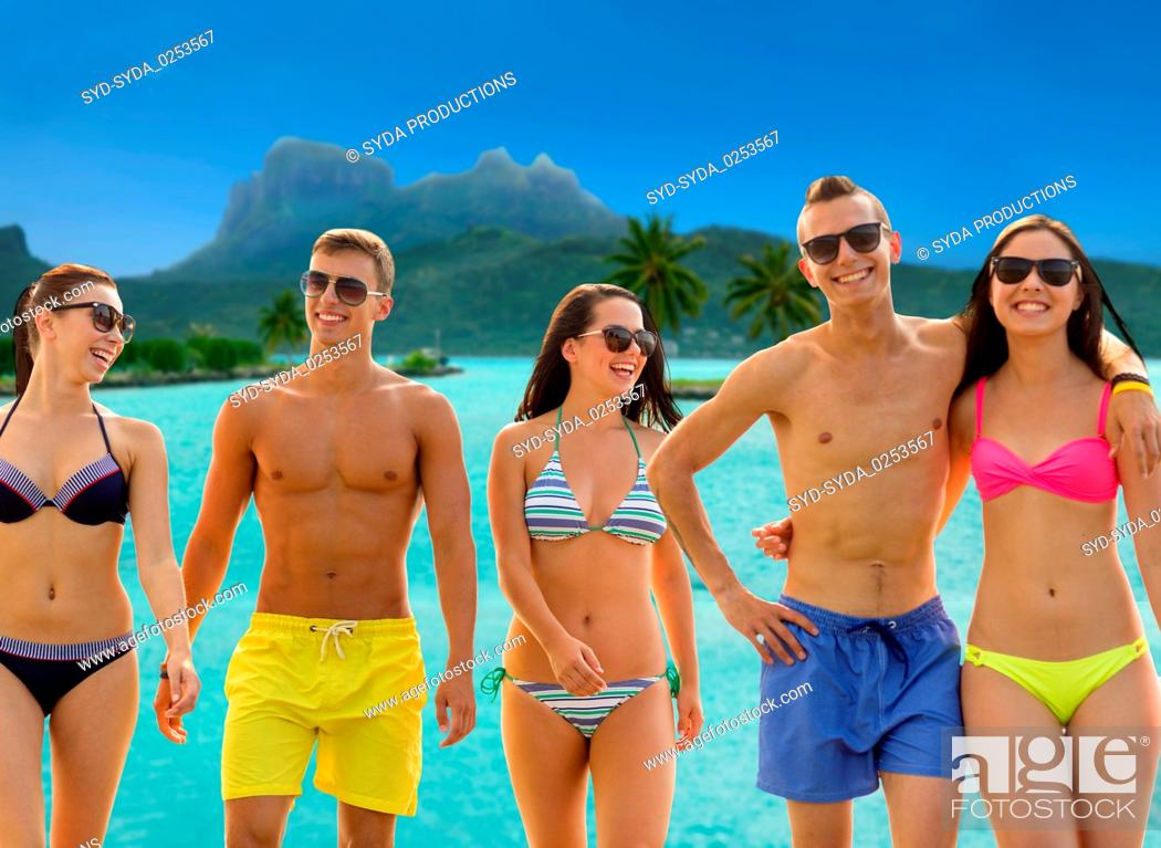 Stock Photo: smiling friends in sunglasses on summer beach.