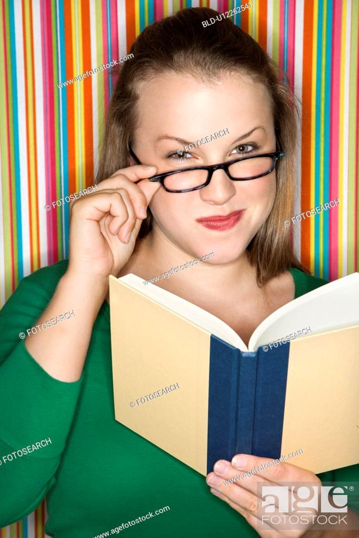 Stock Photo: Young Caucasian female adult reading and looking at viewer over glasses.