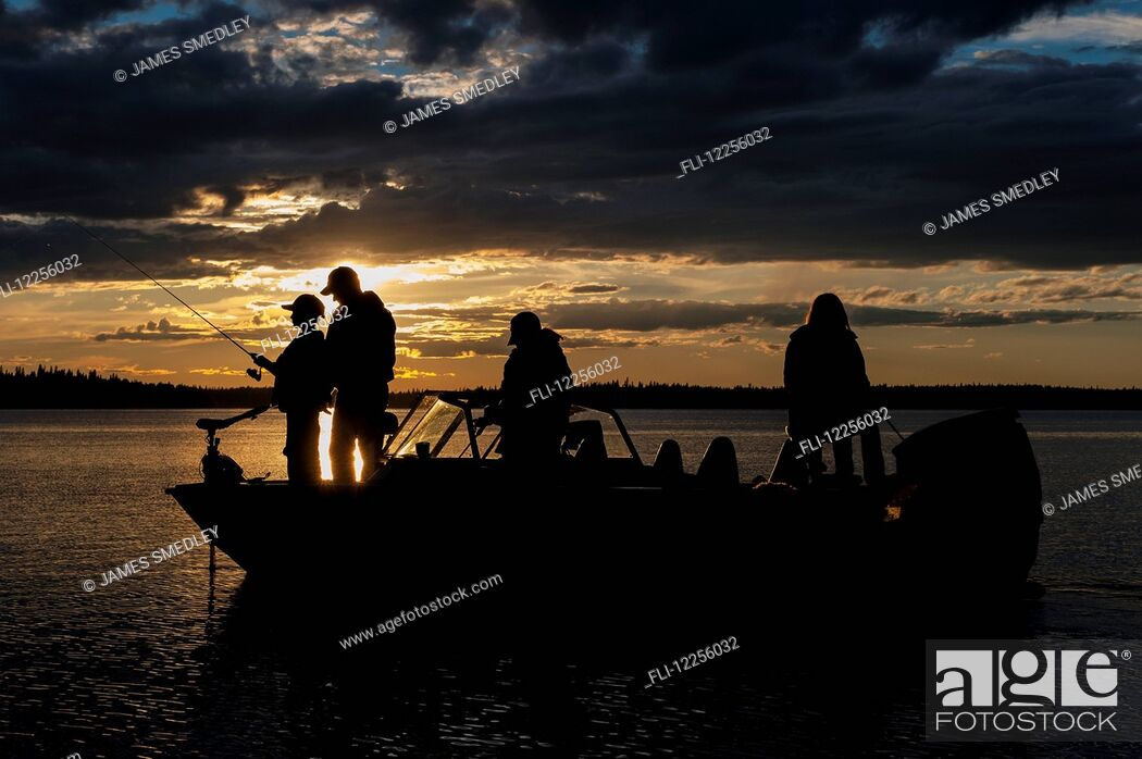 Stock Photo: Silhouette of a family fishing from their motorboat on a lake at sunset in Northern Ontario; Ontario, Canada.