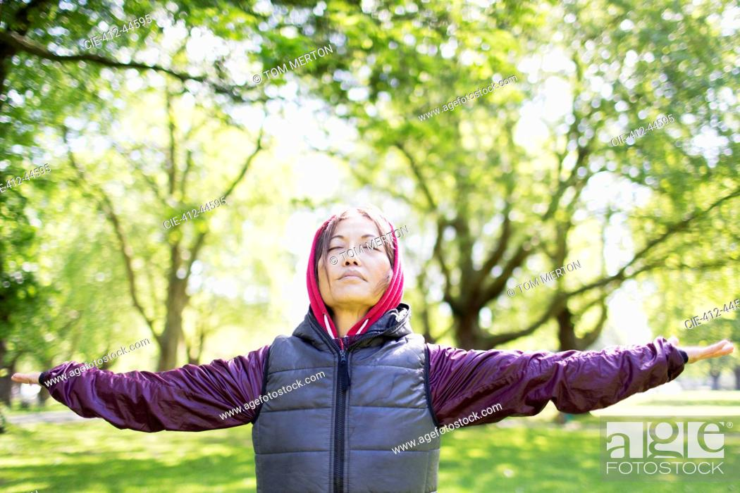 Stock Photo: Portrait serene active senior woman stretching in park.