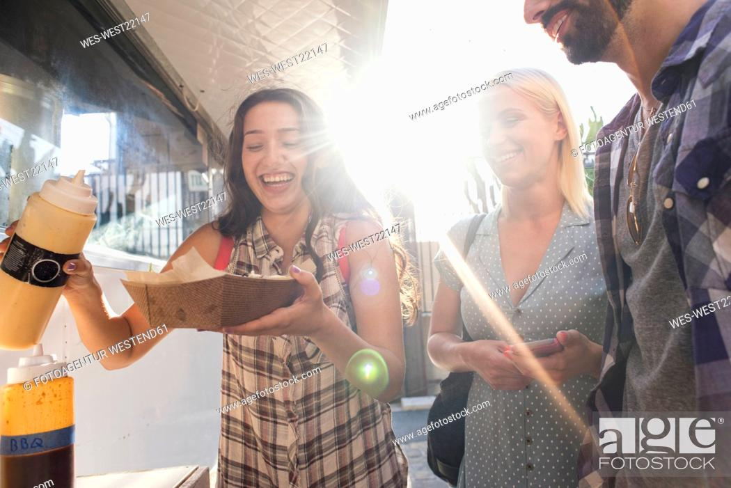 Stock Photo: Happy friends with takeaway food outdoors.