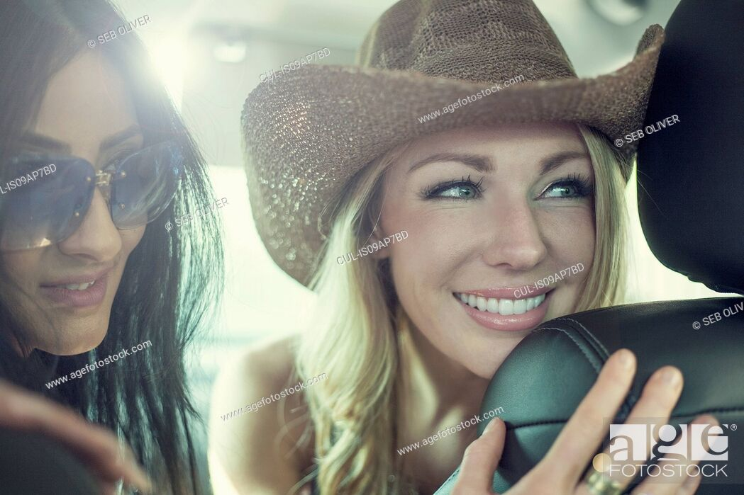 Stock Photo: Two young women looking through car seats in car.
