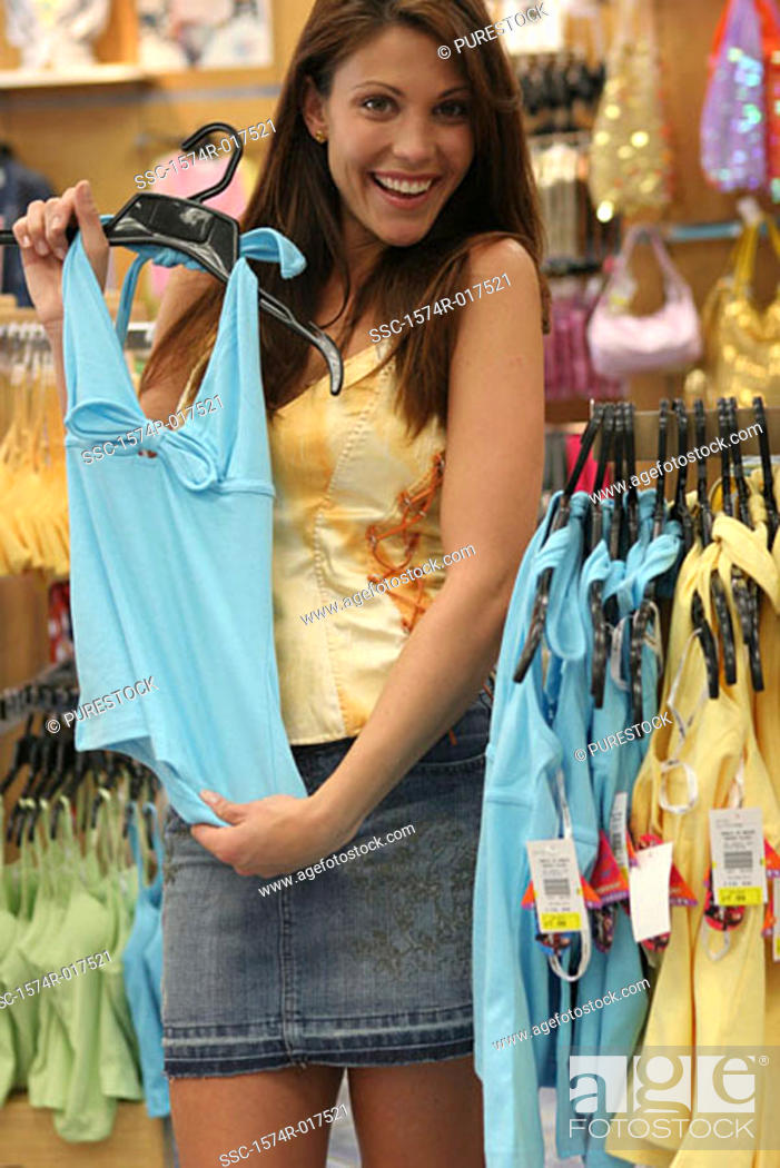 Stock Photo: Portrait of a young woman holding a top in a clothing store.