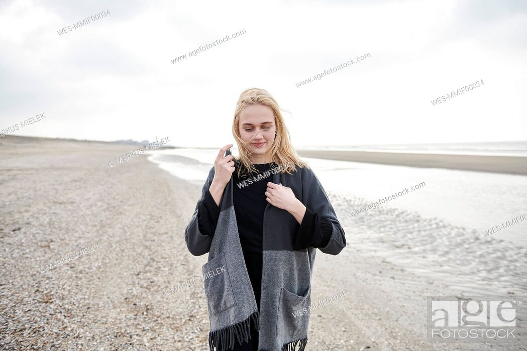 Photo de stock: Netherlands, blond young woman wearing gray jacket on the beach.