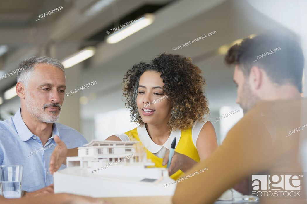 Stock Photo: Architects discussing model in meeting.