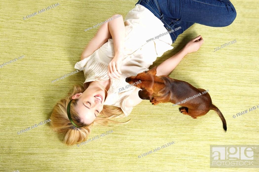 Stock Photo: Young woman playing with dog.