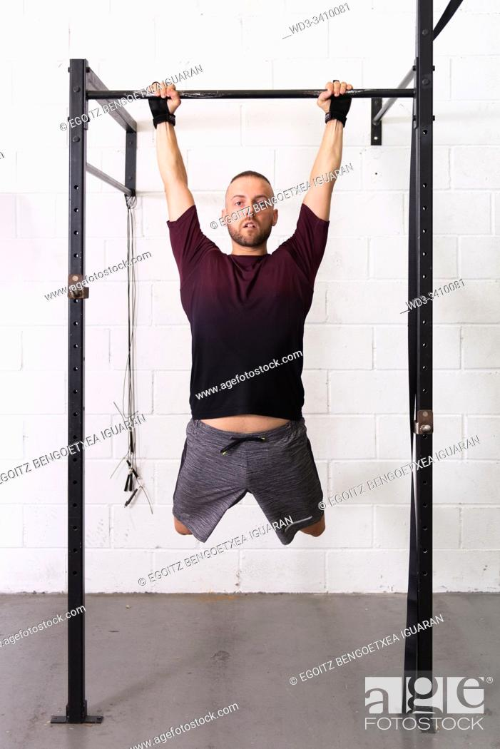 Stock Photo: Young man making pull-ups with white background.