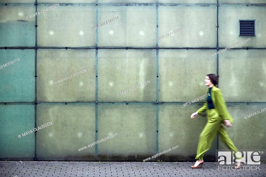 Stock Photo: Businesswoman wearing green suit passing a wall.