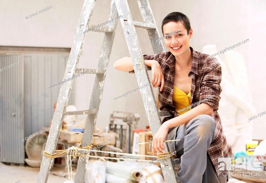 Stock Photo: Female interior decorator sitting on ladder in work site portrait.