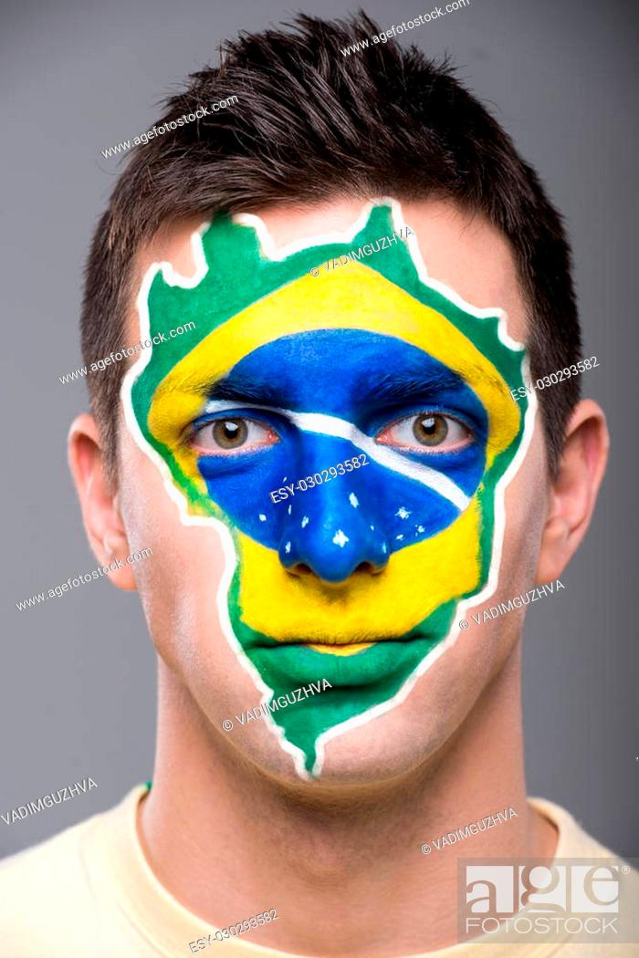 Photo de stock: Portrait of young man with brazilian flag painted on his face.