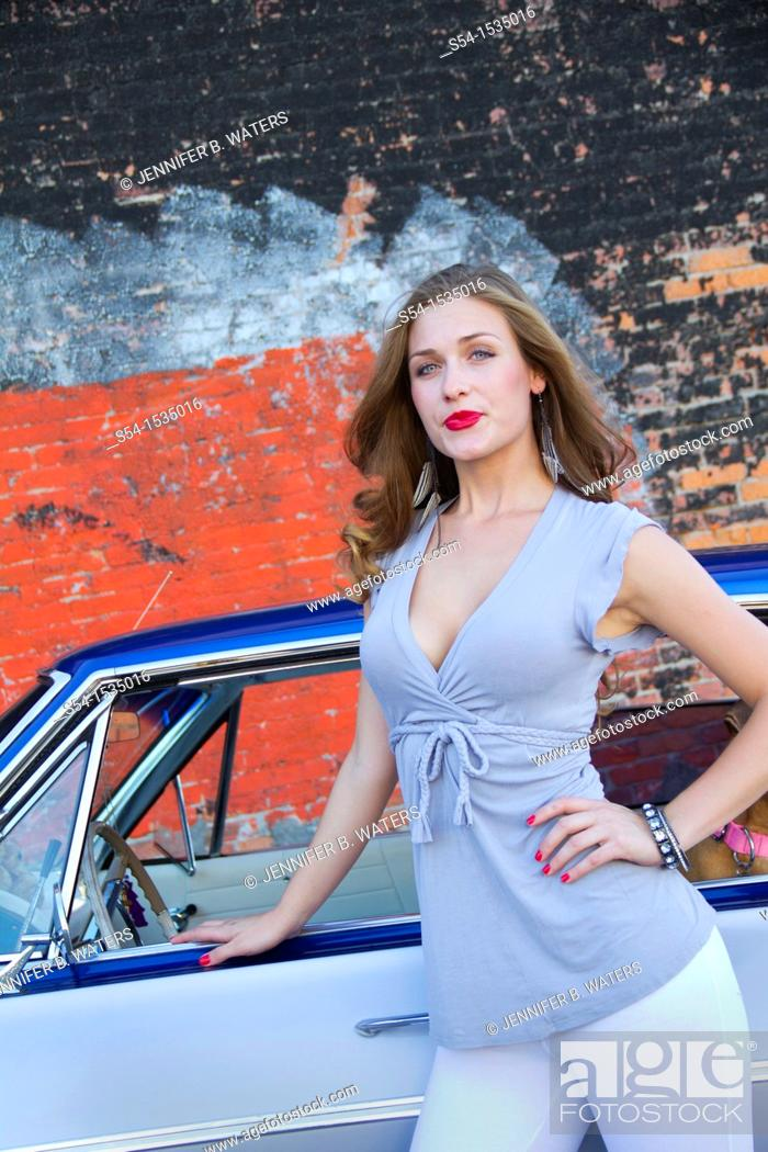 Stock Photo: A young woman with a 1964 Chevrolet Impala in Spokane, Washington, USA.