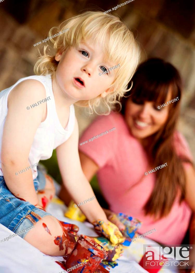 Photo de stock: Cute child painting with vibrant colors in the garden.