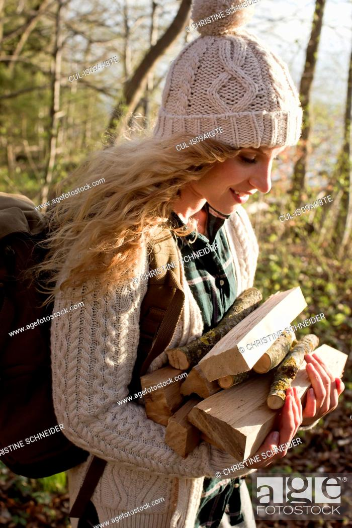 Stock Photo: Woman collecting wood for fire by seaside.