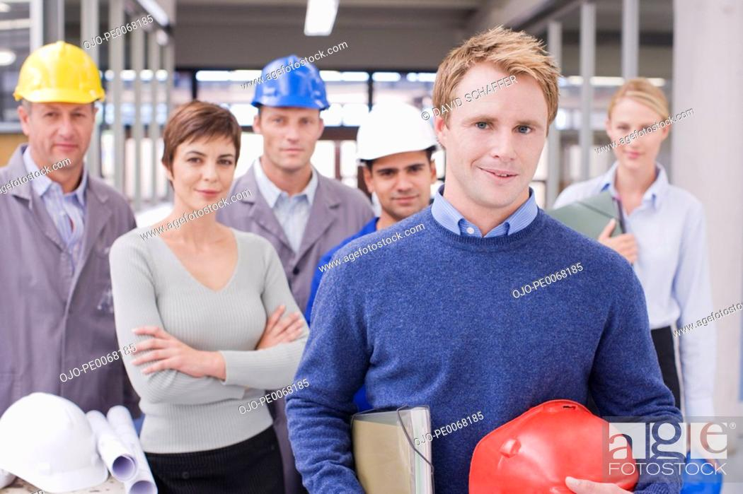 Stock Photo: Business people and construction workers posing.