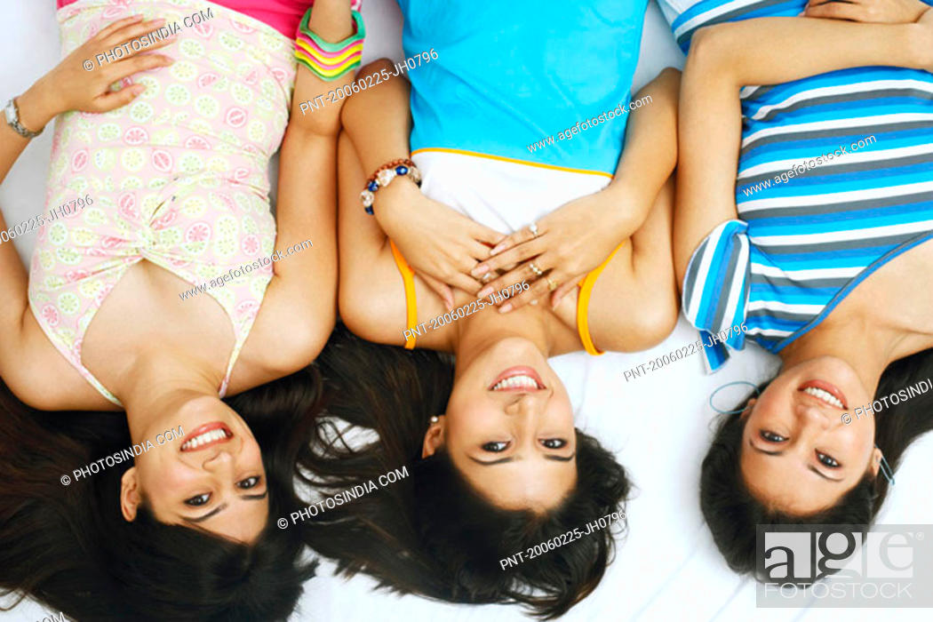 Stock Photo: High angle view of three young women smiling.