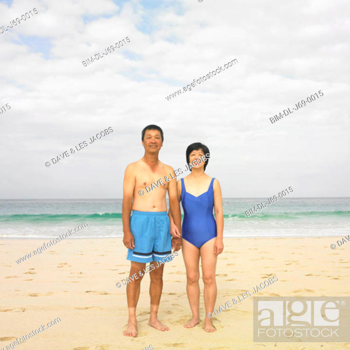 Stock Photo: Couple in bathing suits standing at beach.