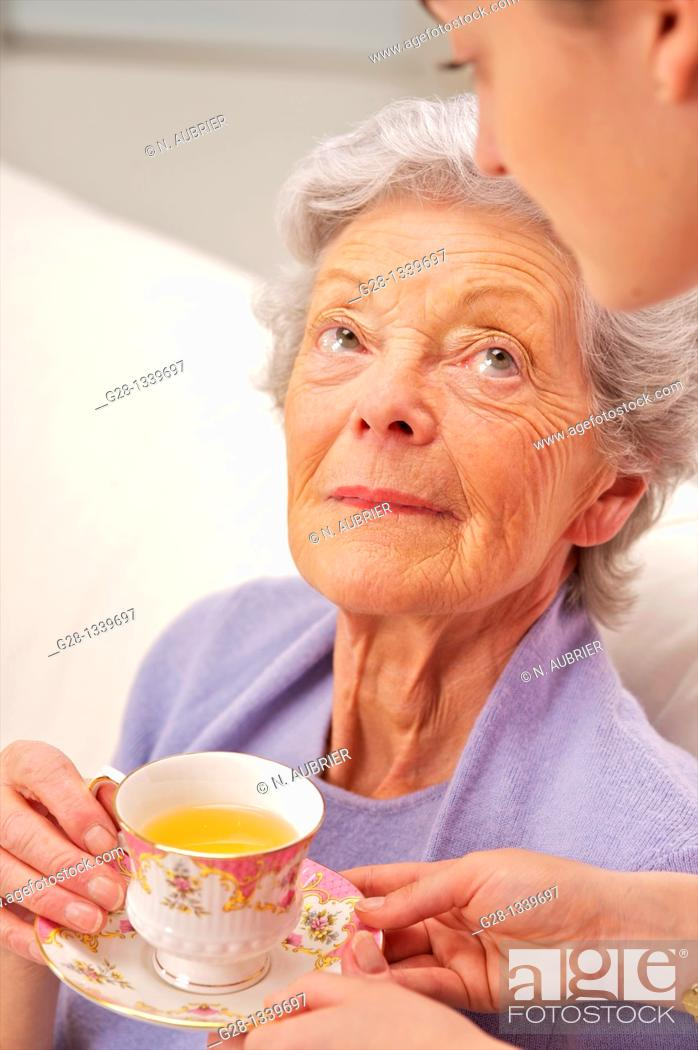 Stock Photo: senior woman in a mauve cardigan, and young help giving her a cup of tea at home.