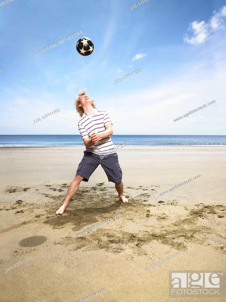 Stock Photo: Young man with football on beach.