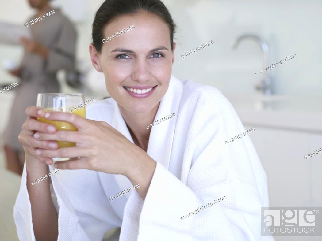 Stock Photo: Woman in robe with orange juice and man in background.