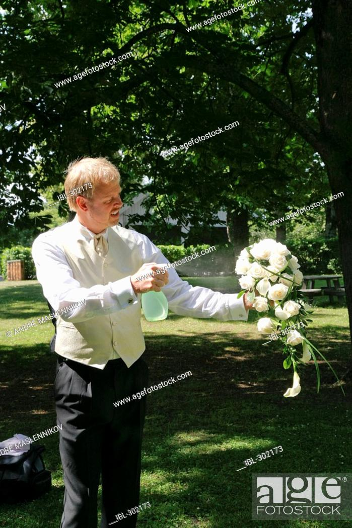 Stock Photo: Bridegroom is spraying the wedding bouquet with water to keep it fresh.