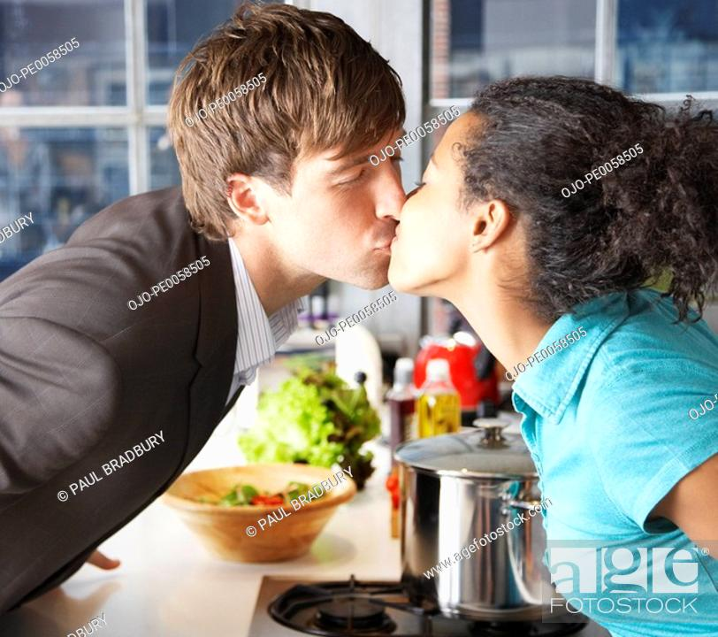 Stock Photo: Couple kissing in kitchen over counter.