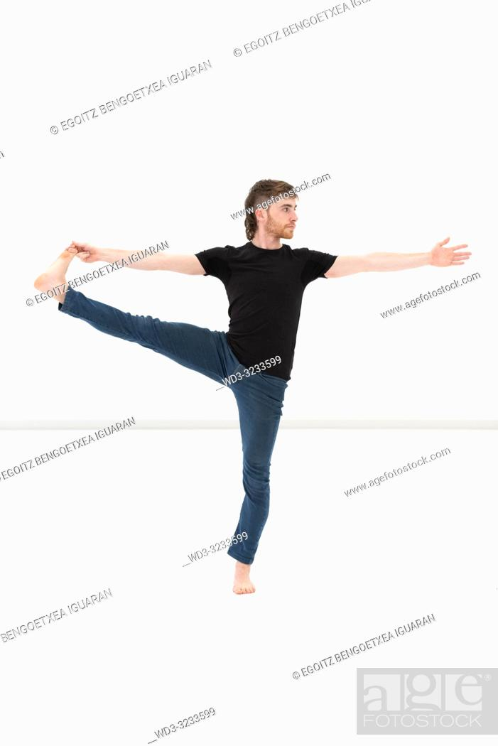 Stock Photo: Casual dressed young adult man making yoga exercises on white background.