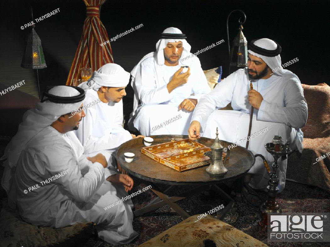 Stock Photo: Arab men playing backgammon in Arabian tent.