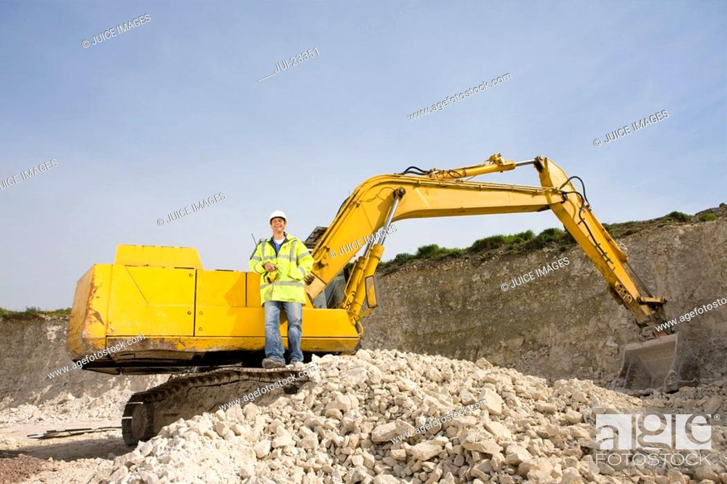 Stock Photo: Construction worker standing on bulldozer in rock pit.