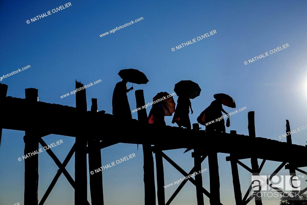 Stock Photo: Buddhist monks silhouetted on the U Bein Bridge, Taungthman Lake, U Bein, Amarapura, Myanmar (Burma), Asia.