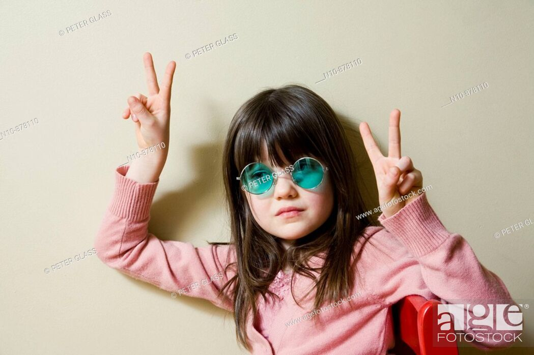 Stock Photo: Young girl wearing green colored sunglasses.