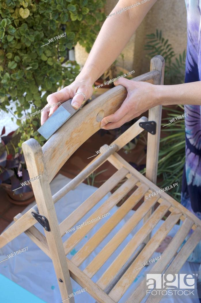Stock Photo: Young woman sanding before painting a chair.