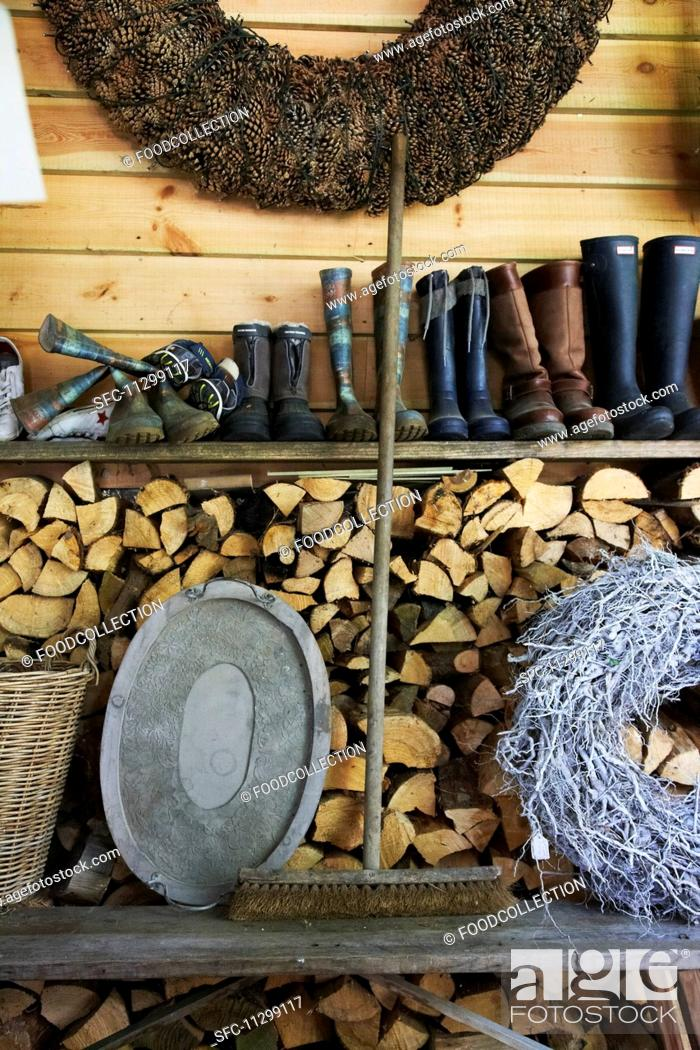 Stock Photo: An old broom between a tray and a woven wreath on a wooden bench in front of a wood pile with a shelf of rubber boots above it.