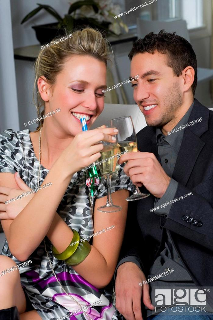 Stock Photo: Young couple toasting with champagne flutes and smiling.