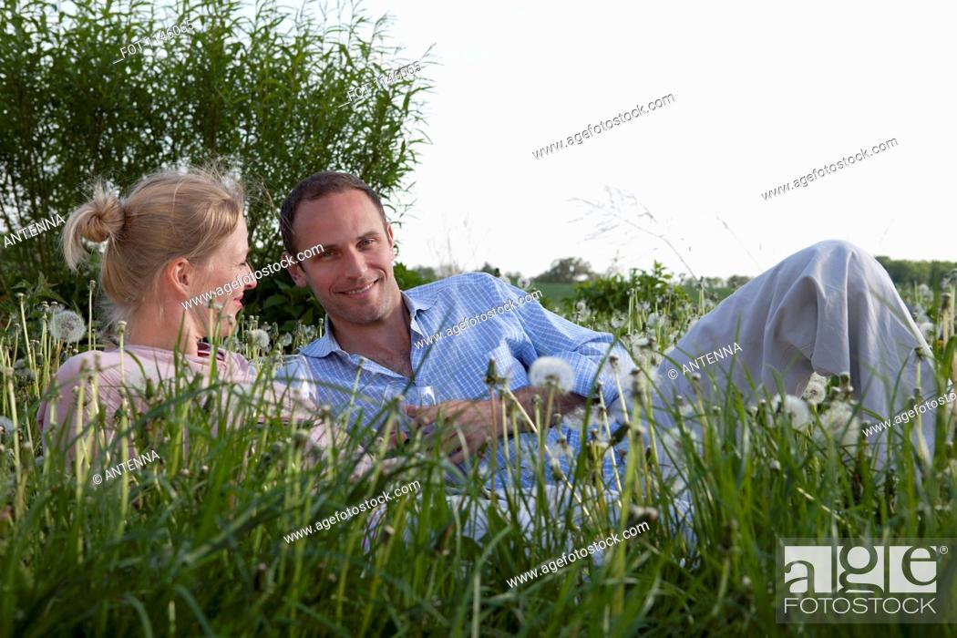 Stock Photo: A couple lying in the grass enjoying some red wine.