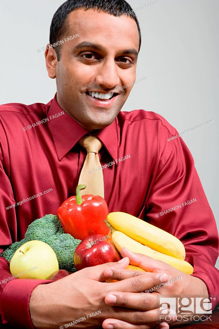 Stock Photo: Man holding fruit and vegetables.