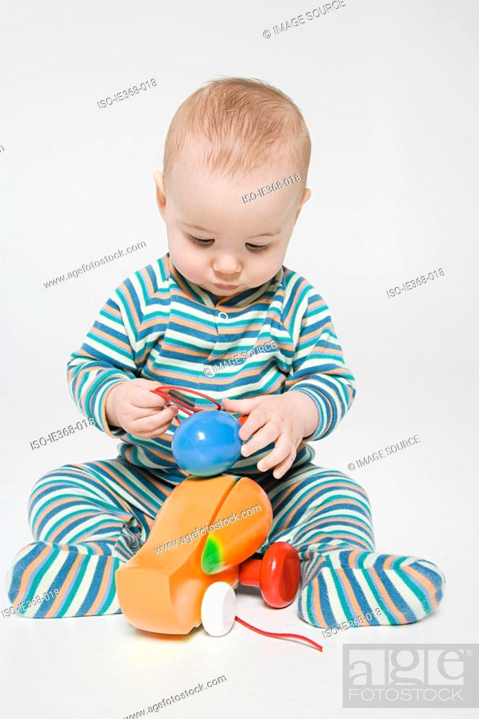 Stock Photo: A baby boy playing with a toy duck.