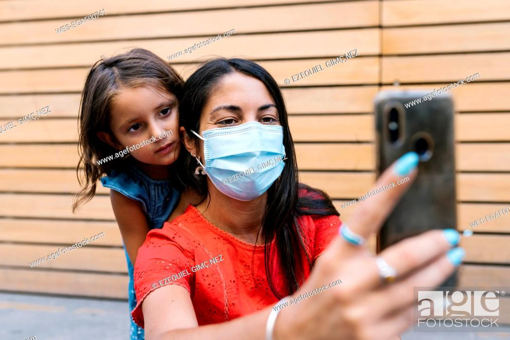 Imagen: Mother wearing mask taking selfie with daughter against wall.