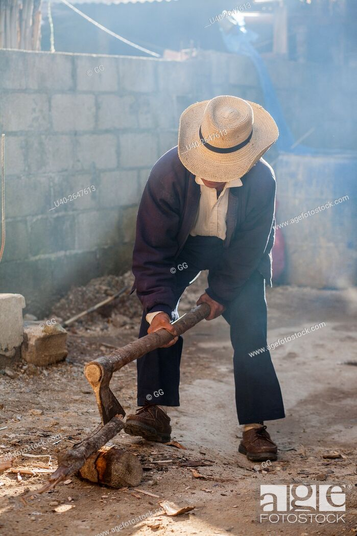 Stock Photo: Guatemala, Poaquil, Mayan man chopping wood.