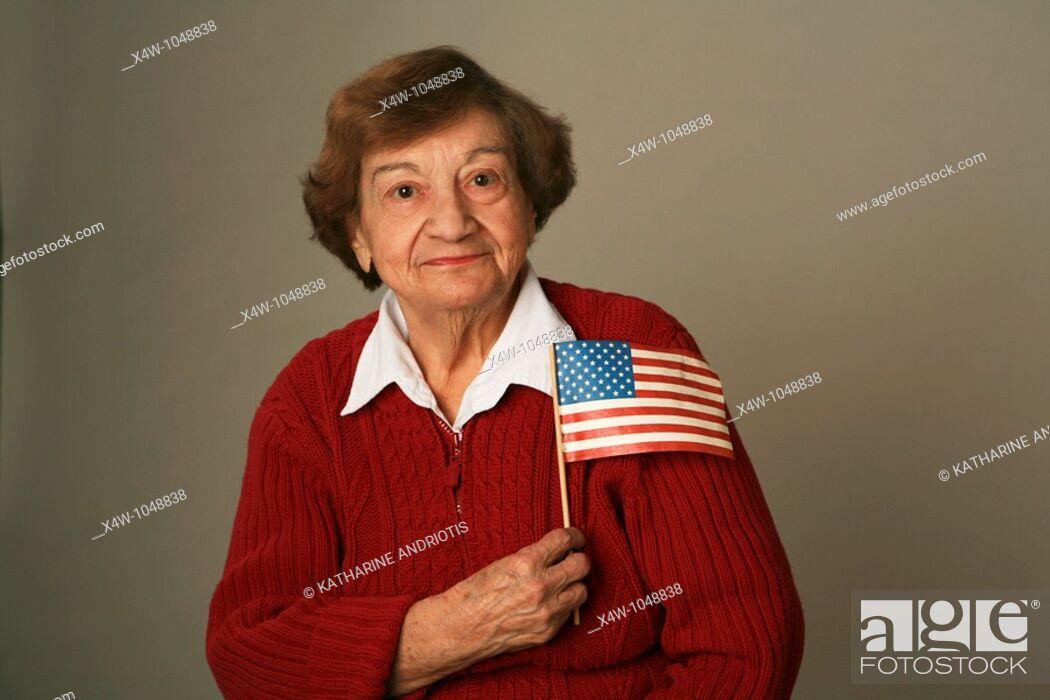 Stock Photo: An American senior woman patriot holding flag.