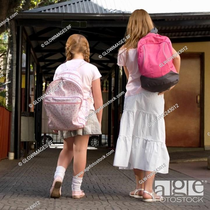 Stock Photo: Rear view of two schoolgirls carrying schoolbags and walking.