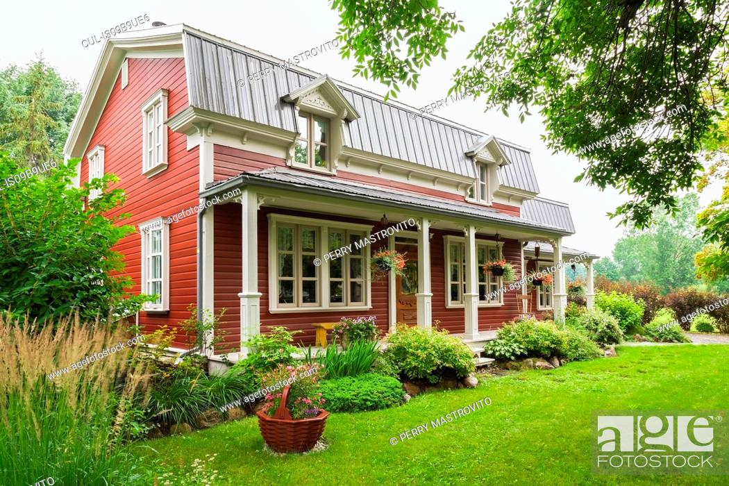 Imagen: Pinewood plank house facade with mansard roof and landscaped garden, Quebec, Canada.