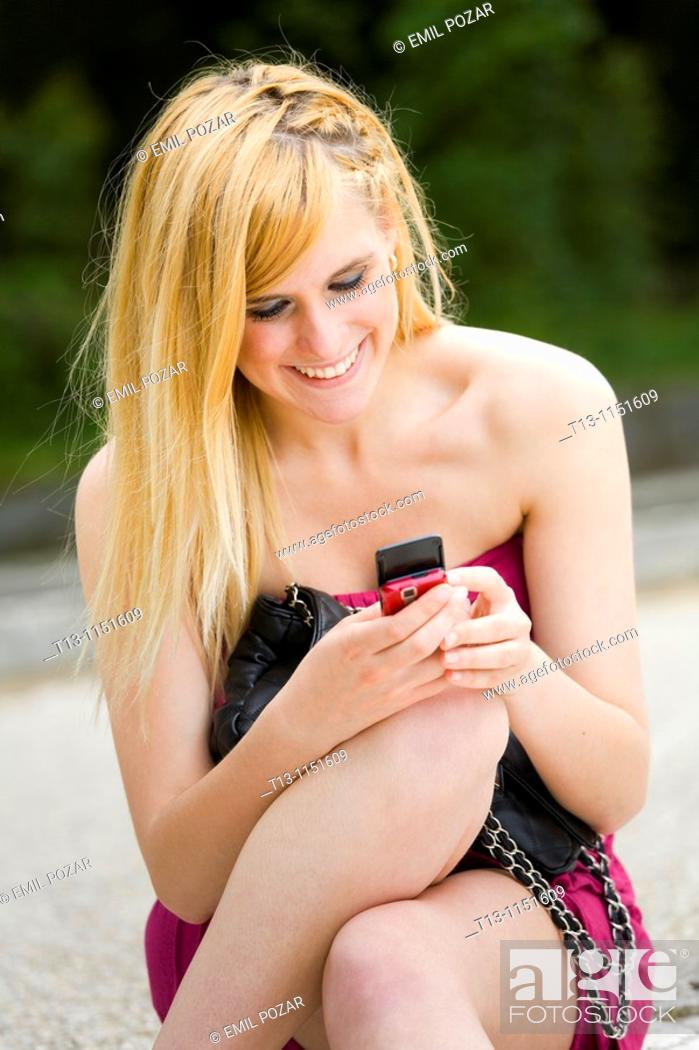 Stock Photo: Happy attractive young woman with a cellular phone in hand.