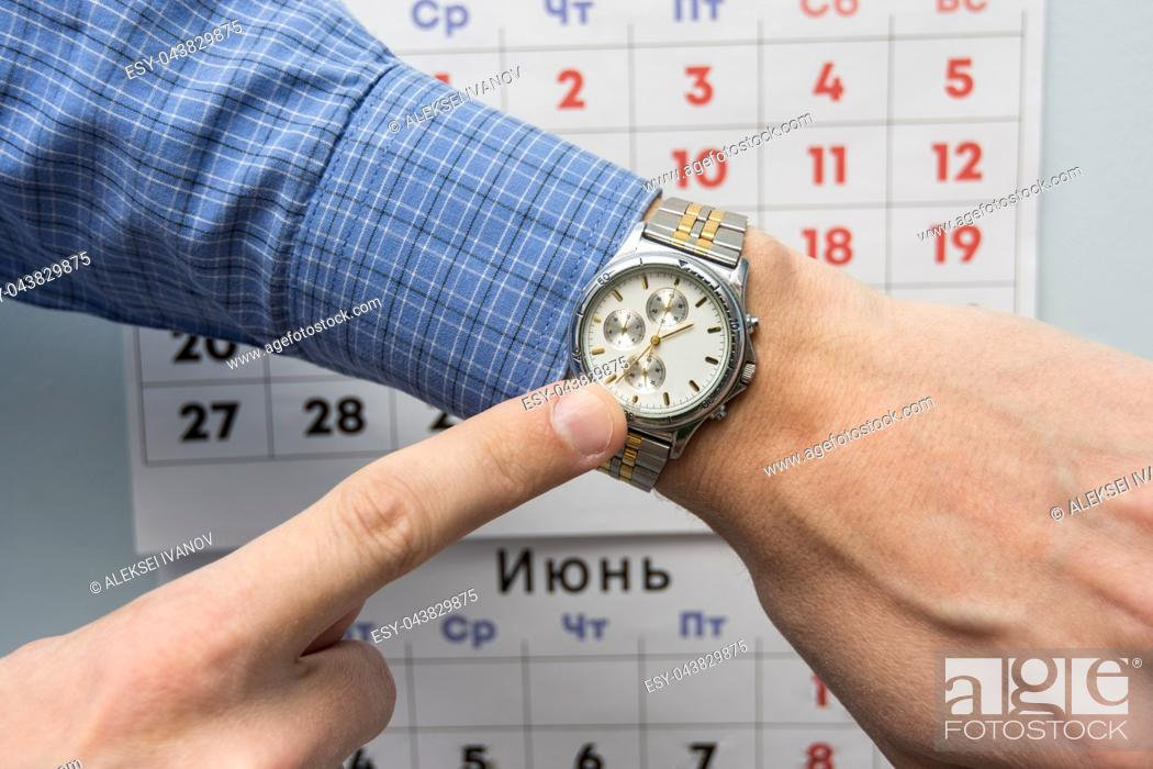 Stock Photo: Office specialist's hand points to a wristwatch, in the background is a wall calendar.
