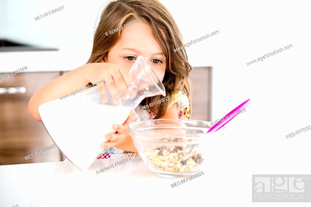 Stock Photo: Germany, Girl pouring milk in muesli.