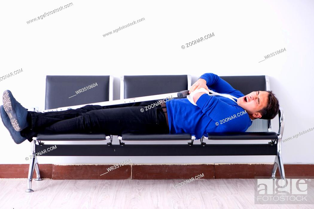 Stock Photo: Desperate man waiting for his appointment in hospital with broken arm.