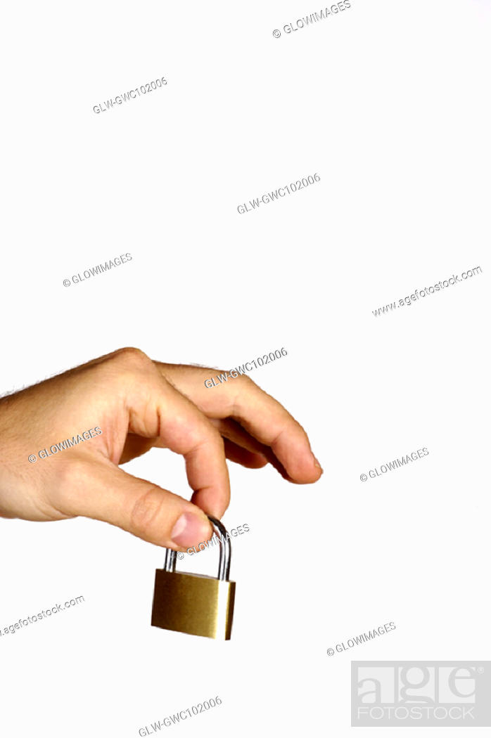 Stock Photo: Close-up of a person's hand holding a padlock.